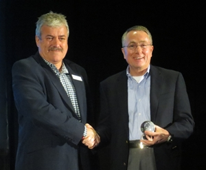 Ian Atkins, left, General Manager of Dominion Marine Media, presents a 2012 YachtWorld Heroes Award to Dusty McCoy, CEO of Brunswick Corporation.