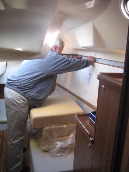 Designer Gerry Douglas flips up the upper bunk in the smaller port cabin. A double berth can be created where he's standing, or, with the cockpit hatch up (as it is in the photo), a sailor can use this area to keep tools and work on projects.