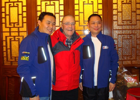 Chinese Motorboat Association Secretary General Wan Honjun, H1 Unlimited Chairman Sam Cole, and Beijing Kingolym Culture Communications President Zhengmin Shi discuss an H1 Unlimited event in China during a recent visit.