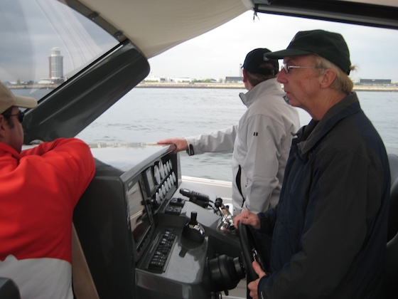 Bump Wilcox of New Wave Yachts handles the helm; see IPS-drive joy stick on the dash; at left, Stanton Murray stands in the companionway to the cabin.
