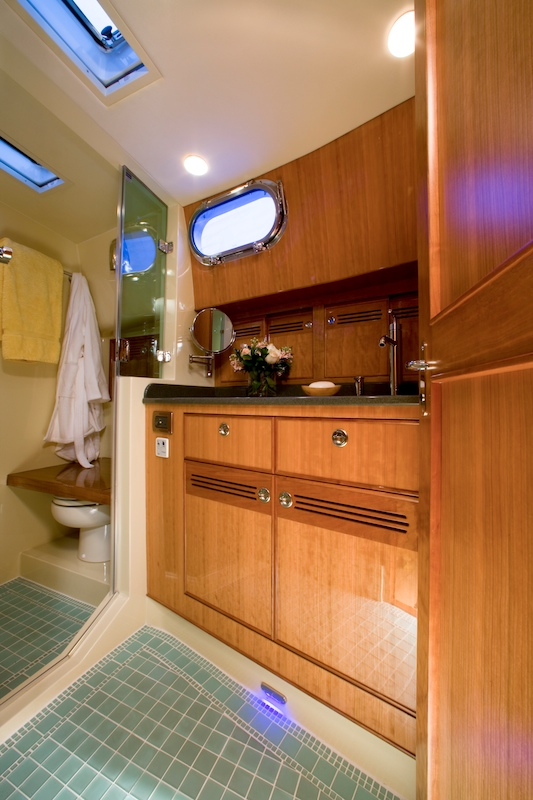 The master stateroom head mixes practical tile and the quarter-sawn cherry featured throughout the interior.